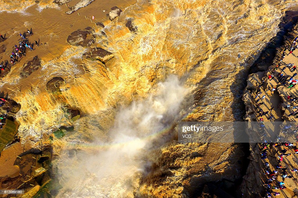 YAN'AN, CHINA - OCTOBER 02: Aerial view of tourists visiting the Hukou Waterfall during the National Day holiday on October 2, 2016 in Yan'an, Shaanxi Province of China. The Hukou Waterfall on the Yellow River attracted thousands of tourists on the second day of the 7-day National Day holiday.