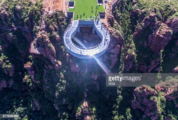 Aerial view of tourists walking on the glass skywalk at Fuxi Mountain tourism area on June 12, 2018 in Xinmi, Henan Province of China. The round...