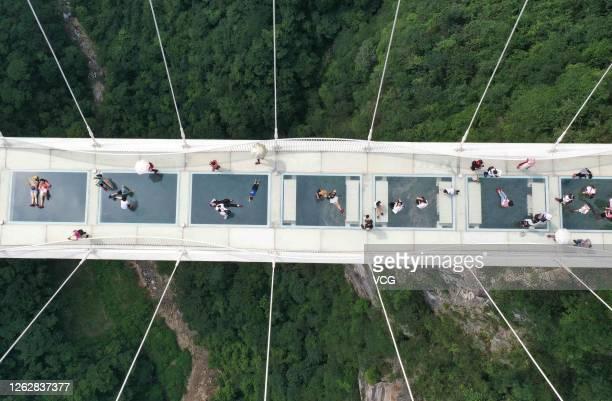 Aerial view of tourists walking on the glass-bottomed bridge at the Zhangjiajie Grand Canyon on July 30, 2020 in Zhangjiajie, Hunan Province of China.