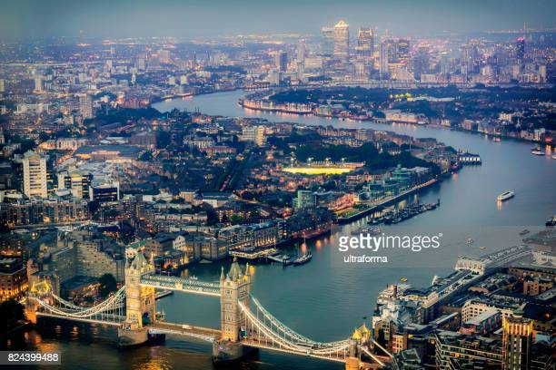 aerial view of tower bridge and canary wharf at night - river thames stock pictures, royalty-free photos & images
