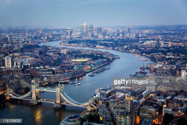 aerial view of tower bridge and canary wharf skyline at night - greater london stock pictures, royalty-free photos & images