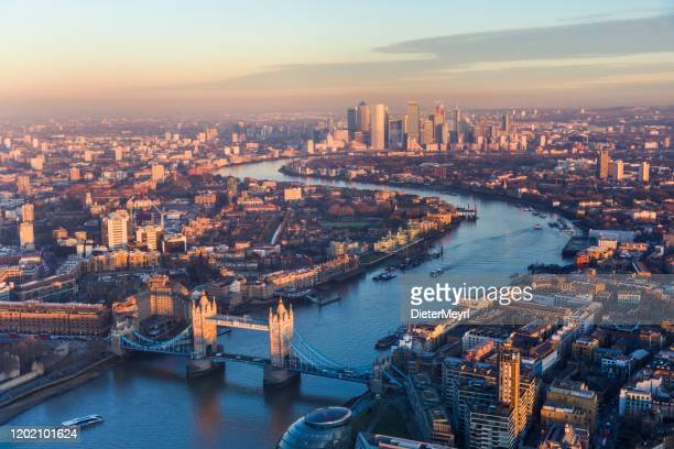 aerial view of tower bridge and canary wharf skyline at sunset - morning stock pictures, royalty-free photos & images