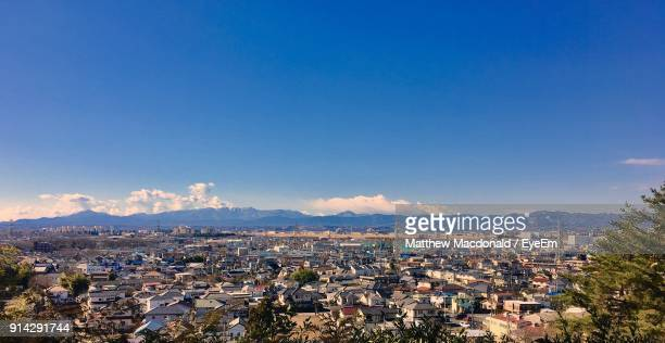 aerial view of town against blue sky - 町 ストックフォトと画像