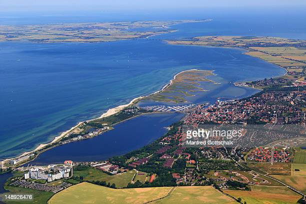 aerial view of town and baltic coast, with steinwarder/graswarder peninsula, binnensee and fehmarn island in background. - fehmarn stock pictures, royalty-free photos & images