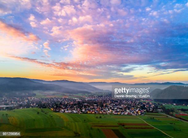 aerial view of town and mountains against cloudy sky during sunset - dämmerung stock-fotos und bilder