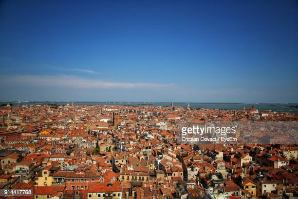 Aerial View Of Town By Sea Against Blue Sky