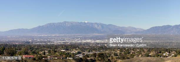 aerial view of townscape and mountains against clear blue sky - san bernardino california stock pictures, royalty-free photos & images