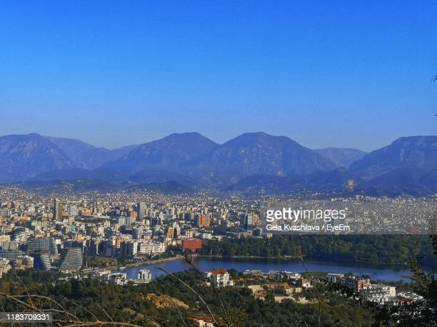 aerial view of townscape by mountains against clear blue sky - tirana stock pictures, royalty-free photos & images