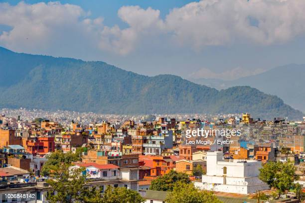 aerial view of townscape by mountains against sky - kathmandu stock pictures, royalty-free photos & images
