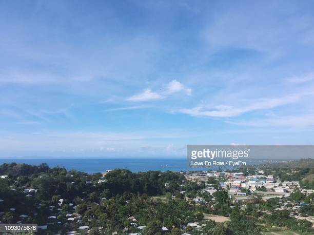aerial view of townscape by sea against blue sky - solomon islands stock pictures, royalty-free photos & images