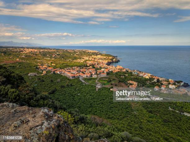 aerial view of townscape by sea against sky - acireale stock-fotos und bilder