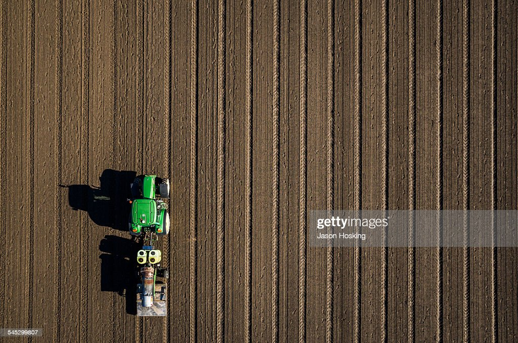Aerial view of tractor driving over bare dirt : Foto de stock