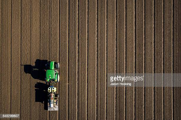 aerial view of tractor driving over bare dirt - tractor stock pictures, royalty-free photos & images