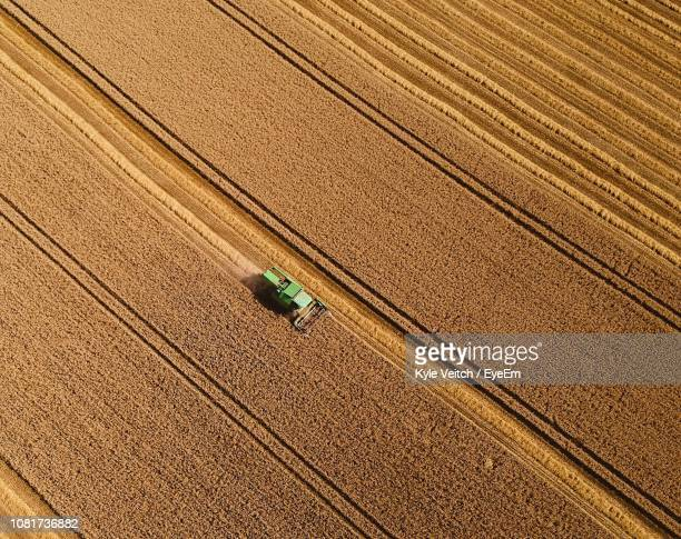 aerial view of tractor on field - cultivated land stock pictures, royalty-free photos & images