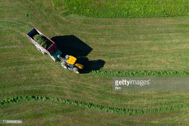 aerial view of tractor with trailer collecting grass - tractor stock pictures, royalty-free photos & images