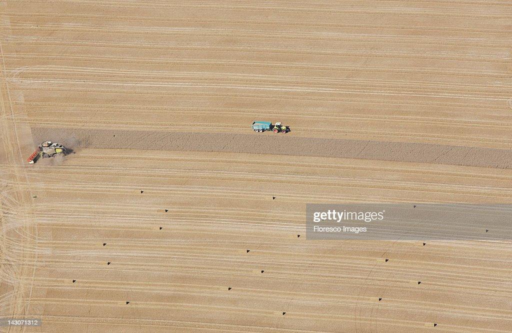 Aerial view of tractors at work in crop fields : Bildbanksbilder
