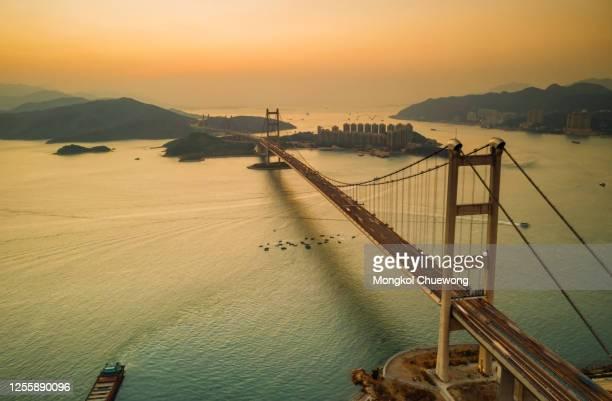 aerial view of traffic of car at tsing ma bridge in tsing yi area of hong kong at sunset. - つり橋 ストックフォトと画像