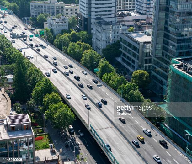 aerial view of traffic on road junction in modern city - prosperity stock pictures, royalty-free photos & images