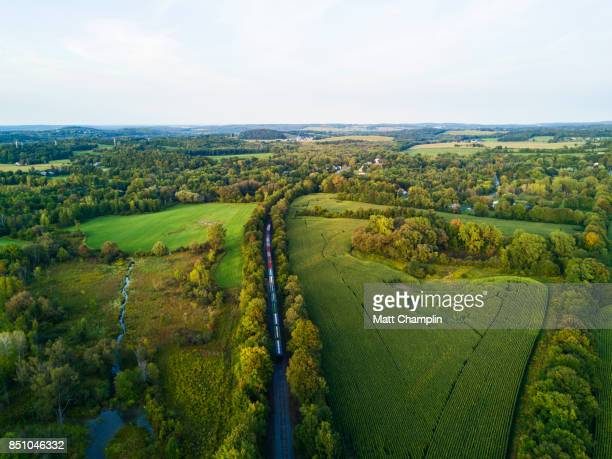 aerial view of train on tracks going through rural countryside - finger lakes stock pictures, royalty-free photos & images
