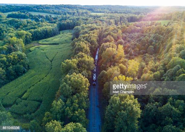 aerial view of train on tracks going through rural countryside - 貨物列車 ストックフォトと画像