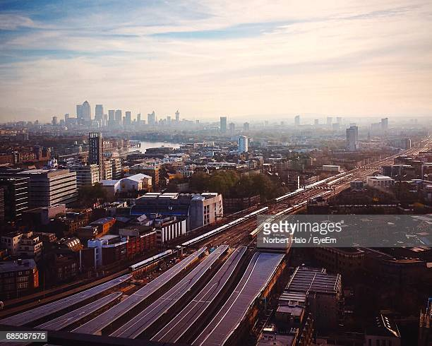Aerial View Of Trains Moving On Railroad Track By Cityscape Against Cloudy Sky