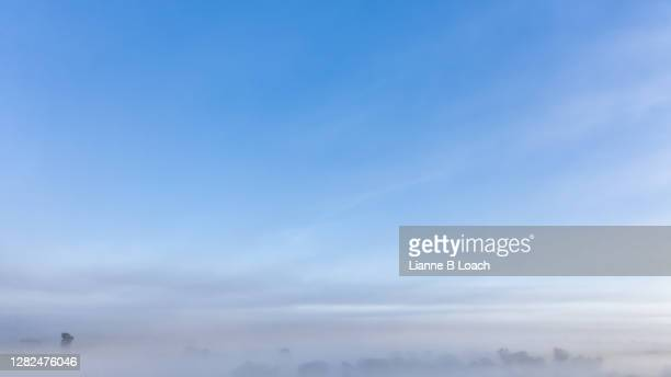 aerial view of tranquil fog over farmland. soft blue sky with fog sweeping to the right of the frame. - lianne loach stock pictures, royalty-free photos & images