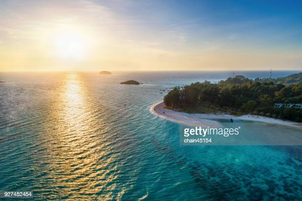 aerial view of tropical island with sandy beach, palm, coconut among clear ocean. this aerial view from lipe island, beautiful beach and island in south of thailand. blue ocean with coral. - indian ocean stock pictures, royalty-free photos & images