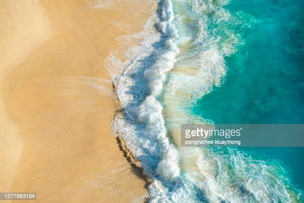 aerial view of turquoise ocean wave reaching the coastline. - wave stock pictures, royalty-free photos & images