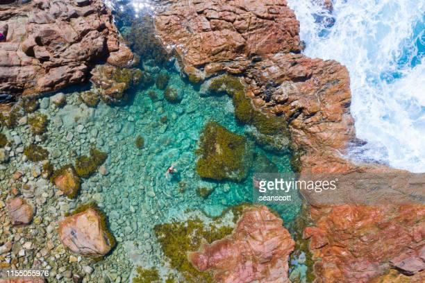 aerial view of two children swimming in an ocean rock pool, australia - tidvattensbassäng bildbanksfoton och bilder