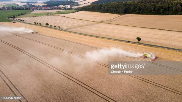 Aerial view of two combine harvester harvesting a wheat field in midsummer in Germany Due to the drought the harvest seems to be bad for German...