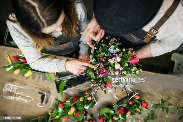 aerial view of two florists preparing bouquet - フラワーアレンジメント ストックフォトと画像