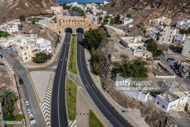 aerial view of two lanes of al bahri road passing below the muscat gate in old muscat, oman - muscat governorate stock pictures, royalty-free photos & images