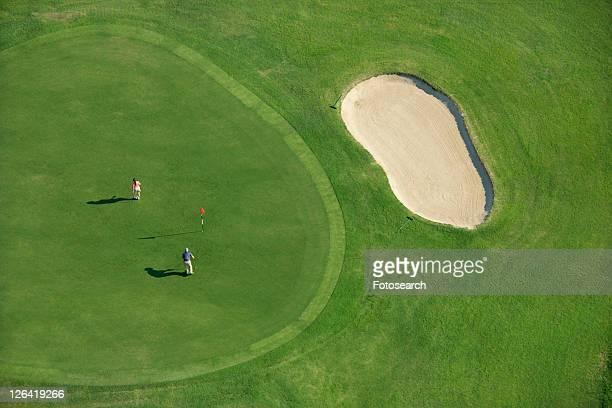 aerial view of two people playing golf at bald head island, north carolina. - 女子 ゴルフ ストックフォトと画像