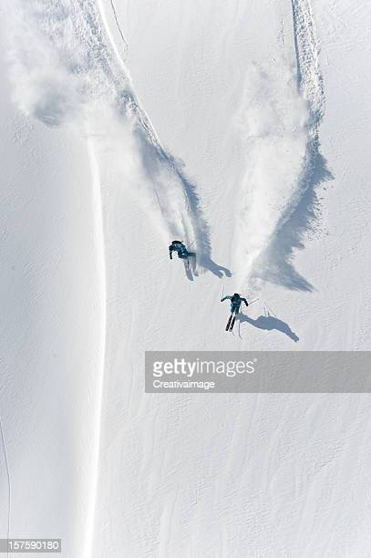 Aerial view of two skiers skiing downhill in powder snow