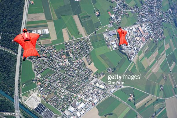 Aerial view of two wingsuit flyers in red suits flying above landscape