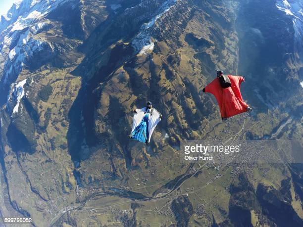 aerial view of two wingsuit flyers, one on his back facing one in red suit flying above landscape - match sport stockfoto's en -beelden