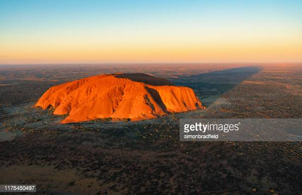aerial view of uluru in the evening sun - uluru stock pictures, royalty-free photos & images