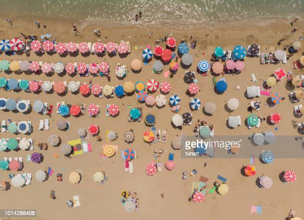 aerial view of umbrellas in a beach of aegean sea - mediterranean sea stock pictures, royalty-free photos & images