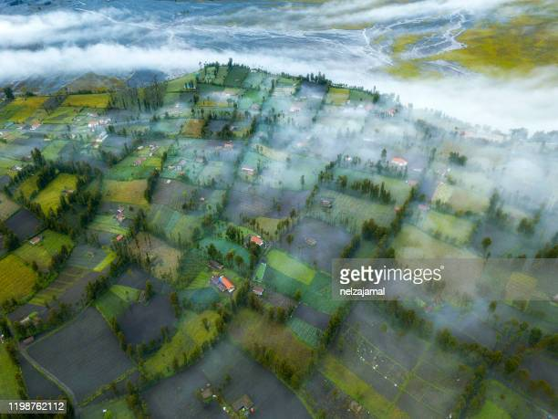 aerial view of unidentified village at mount bromo with dramatic morning fog. - bromo tengger semeru national park stock pictures, royalty-free photos & images