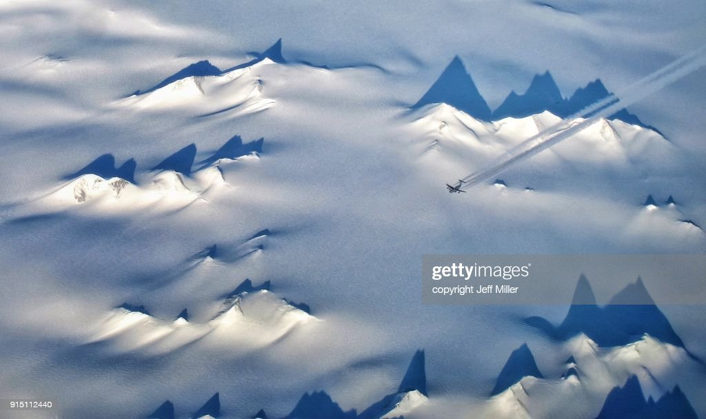 Aerial view of US Air Force C-17 flying over mountains and glaciers of Victoria Land, Antarctica : Stock Photo