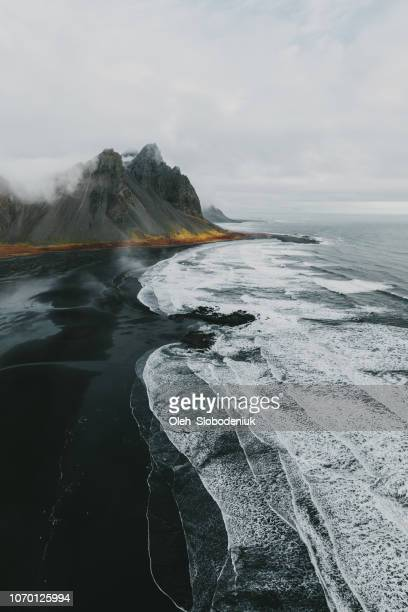aerial view of vestrahorn mountains near the sea - paesaggio spettacolare foto e immagini stock