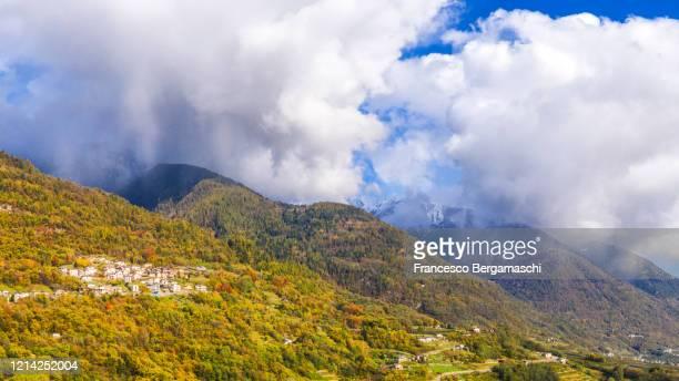 aerial view of village with snowstorm on the mountain in autumn. - italia stockfoto's en -beelden