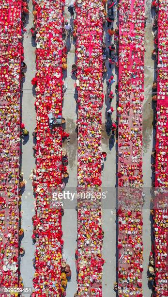 Aerial view of villagers and tourists attending a long table banquet in Longyan Fujian Province of China The longtable banquet is a longheld...
