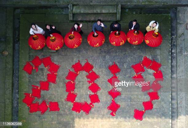 Aerial view of villagers holding red lanterns and a pattern formed by Chinese knots reading '2019' at a scenic spot to welcome the Chinese New Year...