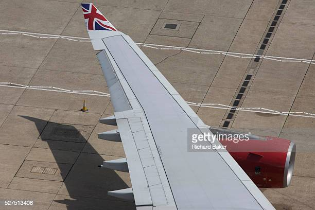 Aerial view of Virgin Atlantic airliner's wing and engine at London Heathrow airport Taxiing along the centreline that helps pilots navigate to...