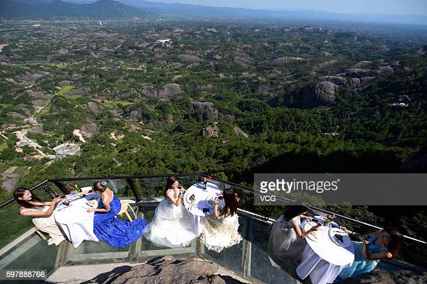 Aerial view of visitors enjoying desserts at an outdoor dining hall on Shiniuzhai's glassbottomed bridge in Pingshan County on August 29 2016 in...