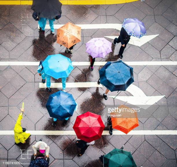 aerial view of walking people using colorful umbrellas in rain - umbrella stock pictures, royalty-free photos & images