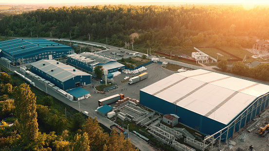 Aerial view of warehouse storages or industrial factory or logistics center from above. Aerial view of industrial buildings at sunset 1001120918