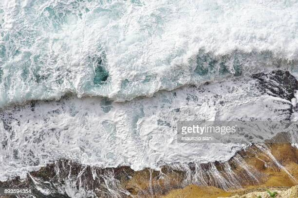 Aerial view of waves coming to cliff coast