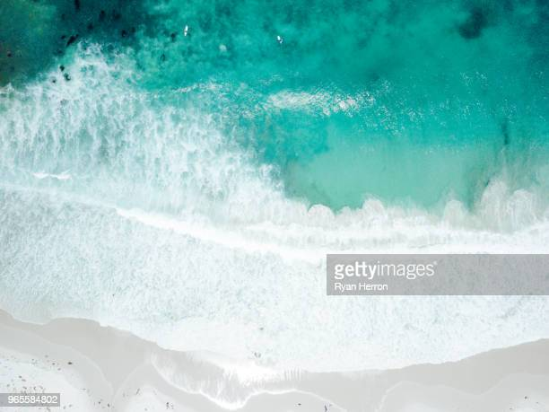 aerial view of waves crashing on sandy beach - california beach stock pictures, royalty-free photos & images